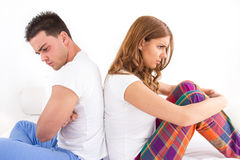 Couple ignoring each other sitting back to back on bed during a stock photo