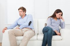 Couple ignoring each other on sofa Stock Photo