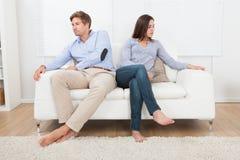 Couple ignoring each other on sofa Royalty Free Stock Photos