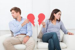 Couple ignoring each other on sofa Stock Photography