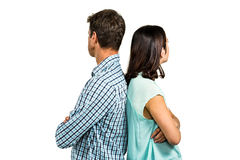 Couple ignoring each other while standing back to back. Against white background Stock Image