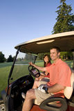 Couple In Cart On Golf Course - Vertical Stock Photo