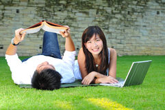 Couple In Love In The Park Reading And Surfing Stock Photo