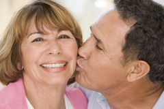 Couple indoors smiling and kissing Royalty Free Stock Image