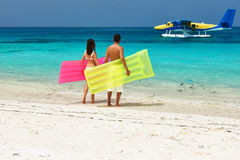 Couple with inflatable rafts looking at seaplane on beach Stock Images