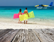 Couple with inflatable rafts looking at seaplane on beach Royalty Free Stock Photo