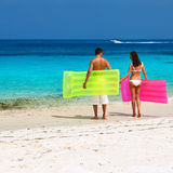 Couple with inflatable rafts on a tropical beach Stock Photography