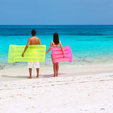 Couple with inflatable rafts on a tropical beach Stock Images