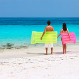 Couple with inflatable rafts on a tropical beach Stock Photos