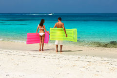 Couple with inflatable rafts on a tropical beach Royalty Free Stock Photos