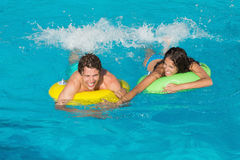 Couple in inflatable rings at swimming pool Royalty Free Stock Image