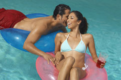 Couple In Inflatable Rings Whispering At Pool Stock Photo