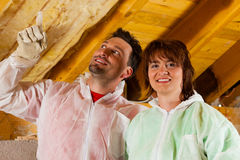 Couple installing thermal insulation to roof Royalty Free Stock Photography