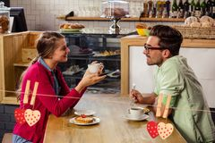 Couple interacting with each other while having coffee. In cafeteria Royalty Free Stock Image