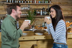 Couple interacting each other while having coffee at counter Stock Photo