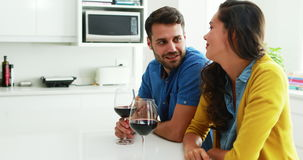 Couple interacting with each other while having glasses of red wine in the kitchen. At home stock video footage