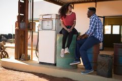 Couple interacting with each other at petrol pump station. Happy couple interacting with each other at petrol pump station Royalty Free Stock Photography