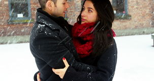 Couple interacting with each other under umbrella. During snowfall stock footage