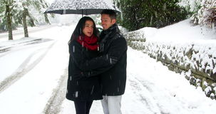 Couple interacting with each other under umbrella. During snowfall stock video