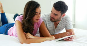Couple interacting with each other while using digital tablet in the bedroom. At home stock video footage