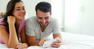 Couple interacting with each other while using digital tablet in the bedroom. At home stock footage