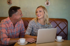 Couple interacting with each other while using laptop in restaurant. Smiling couple interacting with each other while using laptop in restaurant Stock Images