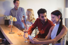 Couple interacting with each other while using mobile phone at bar counter. In restaurant Royalty Free Stock Images