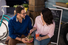 Couple interacting while having snacks and juice. Smiling couple interacting while having snacks and juice Stock Images