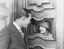 Couple interacting through hole in door. (All persons depicted are no longer living and no estate exists. Supplier grants that there will be no model release Stock Photos