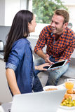 Couple interacting using laptop and digital tablet Royalty Free Stock Photos