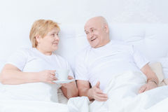 Couple interacts in bed Stock Images