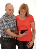 Couple with iPad. Couple standing close together both studying information on screen of iPad held at arms length by man, white background Royalty Free Stock Image