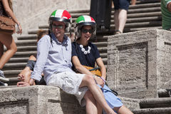 Couple with italian helmet in Spanish Square Steps. A couple is sitting on the steps of Piazza di Spagna in Rome (Italy). They are wearing a helmet in the colors Royalty Free Stock Photos
