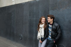 Couple In Jackets Leaning On Wall Stock Images