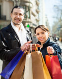 Couple in  jackets with purchases at  street Royalty Free Stock Photography