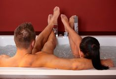 Couple in jacuzzi with feet up. Young couple lying in jacuzzi with feet up, man embracing woman royalty free stock images