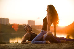 Couple in jeans on the beach. Women sitting like a horsewoman Royalty Free Stock Image