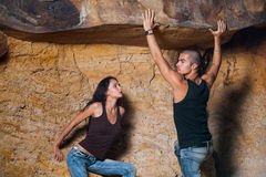 Couple in jeans in the cave. Man holding the rock and protecting his woman Royalty Free Stock Photo