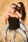 Couple in jeans. Woman threw her heand around his neck Stock Photos