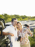 Couple By Jeep With Binoculars. Smiling adult couple standing by jeep with binoculars Royalty Free Stock Photography