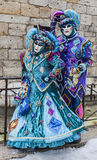 Couple of Jesters. Annecy, France, February 23, 2013: Unidentified couple disguised in blue jesters costumes pose in front of a traditional stone wall in Annecy Royalty Free Stock Images