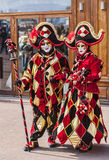Couple of Jesters. Annecy, France, February 24, 2013: Portrait of an unidentified couple disguised in red jesters costumes pose in front of a traditional store Stock Photo