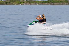 Couple on a jet-ski. From the rear, with white spray Royalty Free Stock Photo