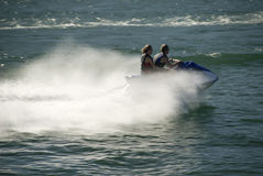 Couple on jet ski on blue-green water. With wake Stock Images