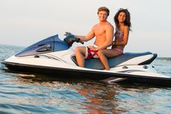 Couple on a jet ski. Multi ethnic couple sitting on a jet ski Stock Image