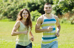 Couple of joggers doing running at park and smiling Royalty Free Stock Photography