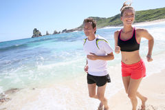 Couple of joggers running on the beach Royalty Free Stock Photo