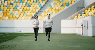 Couple of Joggers on Stadium. Couple of young joggers running on stadium dressed in white t-shirts and black leggins, leisure activity for health stock video footage