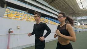 Couple of Joggers on Stadium. Young joggers running on stadium, leisure activity for health stock footage