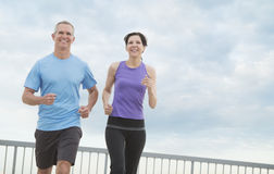 Couple Jogging Against Cloudy Sky Royalty Free Stock Photos